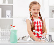 Little girl washing dishes in the kitchen Stock Photography