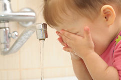 Little girl washing face Stock Photo