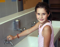 Little girl is washing her hands Stock Image