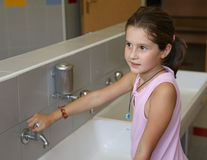 Little girl is washing her hands in the bathroom of the school Royalty Free Stock Images