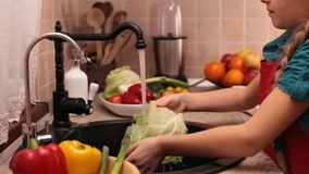 Little girl washing vegetables at the kitchen sink stock video
