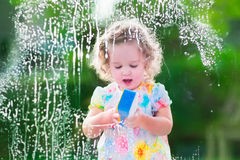 Little girl washing a window Stock Images