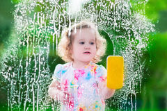 Little girl washing a window. Kids clean the house. Children help at home. Toddler kid cleaning windows and doors standing on a ladder. Child helping with Stock Photos