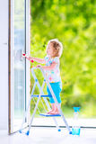 Little girl washing a window in white room Stock Image