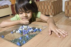 Little girl watch glass marbles Stock Images
