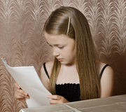 The little girl watches the put sheets of paper Royalty Free Stock Photography