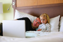 Little girl is watching cartoon with dad while sick. Royalty Free Stock Photography