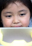 Little girl watching cartoon on mobile device. Stock Photos