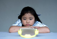 Little girl watching cartoon on mobile device. Stock Photo