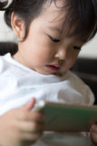 Little girl watching cartoon on mobile device. Stock Images