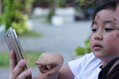 Little girl watching cartoon on mobile device. Royalty Free Stock Photography