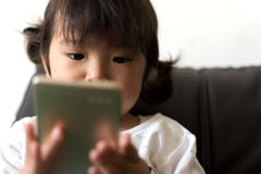 Little girl watching cartoon on mobile device. Royalty Free Stock Image