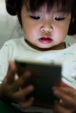 Little girl watching cartoon on mobile device. Royalty Free Stock Images