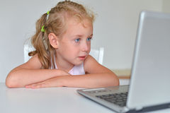 Little girl watching cartoons. Stock Image