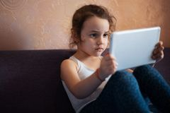 Little girl watching cartoons on the tablet.  royalty free stock photography