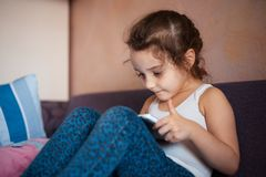 Little girl watching cartoons on the tablet.  stock photos