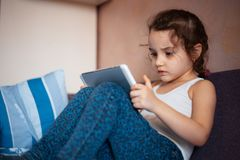 Little girl watching cartoons on the tablet.  royalty free stock photo