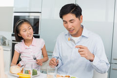Little girl watching father eat food with a fork in kitchen Stock Photos