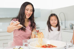 Little girl watching happy woman serve spaghetti in kitchen. Little girl watching happy women serve spaghetti in the kitchen at home royalty free stock photos