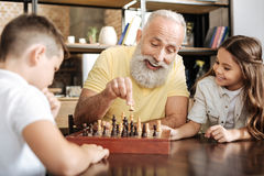 Little girl watching her brother and grandfather play chess. Interesting game. Adorable little girl sitting next to her grandfather and watching him play chess Royalty Free Stock Photo