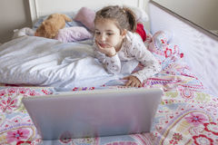 Little girl watching movies with a laptop in bed Royalty Free Stock Photos