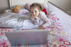Little girl watching movies with a laptop in bed Stock Photos