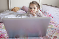 Little girl watching movies with a laptop in bed Royalty Free Stock Photography