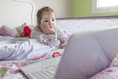 Little girl watching movies with a laptop. Looks distracted Royalty Free Stock Photos