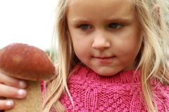 Little girl watching the mushroom. Of the type boletus (fungus stock images