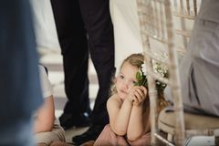 Little Girl Watching People at a Wedding. Little girl is sitting on the dancefloor by a table at a wedding. She is watching the bride and groom share their first Royalty Free Stock Image