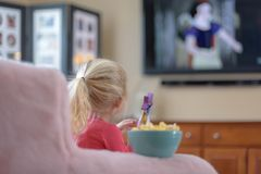 Little girl watching a princess movie on TV at home. Little girl with blonde ponytail watching a movie on TV at home Stock Photography