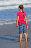 Little girl watching the sea. Full body back view of a blond Caucasian preteen girl child with a stick in her hand standing barefoot in the sand watching the Stock Images