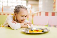 Little girl watching on sugar caramel in plate. Little girl watching on handmade sugar caramel in plate, development of willpower. Fresh lollipop in candy store Royalty Free Stock Photos
