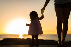 Little girl watching the sunset with her mother on the beach. Silhouette stock images
