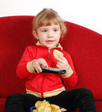 Little girl watching tv. And eating chips Stock Images