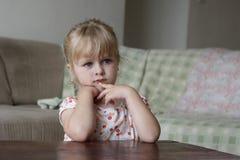 Little girl watching TV. Horizontal photo of a 3 year old blond girl watching TV Stock Photo