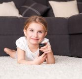 Little girl watching TV. At home Stock Photography