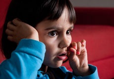 Little girl watching tv alone. Little girl concentrated watching tv alone with the eyes and mouth opened Stock Photo