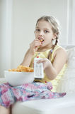 Little girl watching TV as she eats wheel shape snack pellets Royalty Free Stock Photography