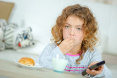 Little girl watching TV as she has breakfast. Little girl watching TV as she has her breakfast Royalty Free Stock Photos