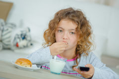 Little girl watching TV as she has breakfast. Little girl watching TV as she has her breakfast Stock Images