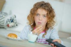 Little girl watching TV as she has breakfast. Little girl watching TV as she has her breakfast Stock Photo