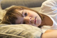 Little girl watching TV. On the couch stretched Royalty Free Stock Photos