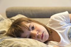 Little girl watching TV. On the couch stretched Royalty Free Stock Images