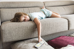 Little girl watching TV. On the couch stretched Stock Image