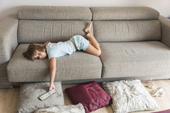 Little girl watching TV. On the couch stretched Stock Photos
