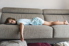 Little girl watching TV. On the couch stretched Royalty Free Stock Photography