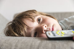 Little girl watching TV. On the couch stretched Royalty Free Stock Image