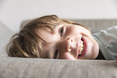 Little girl watching TV. On the couch stretched Stock Photography