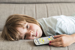 Little girl watching TV. On the couch stretched Royalty Free Stock Photo